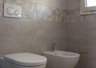 rivestimento effetto cemento chiaro posato in lavanderia